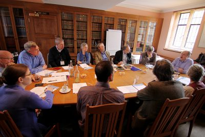 Scholars gathering around a conference table with John Butt