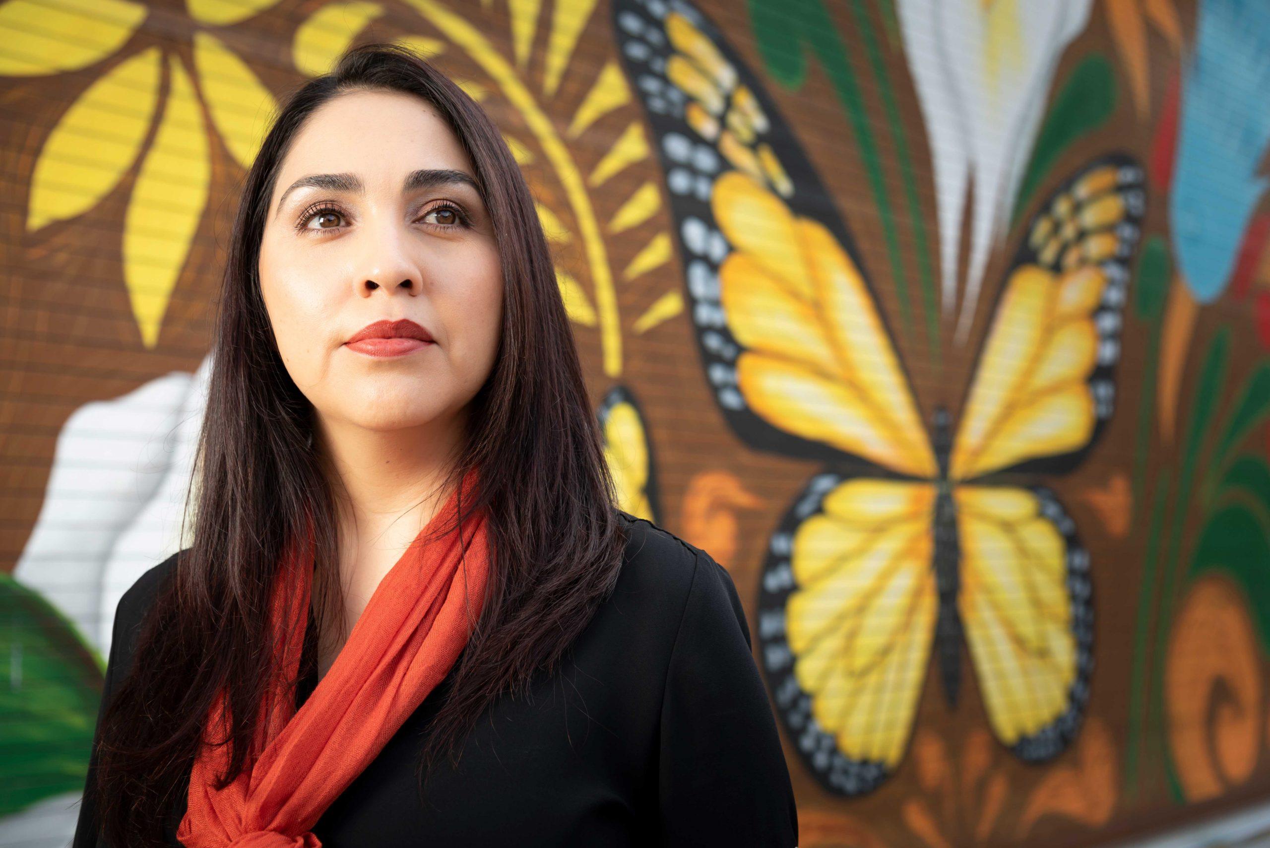 Alma Tinoco Ruiz in front of Mexican culture mural