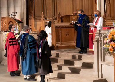 Professor David Emmanuel Goatley and Chaplain Meghan Benson bless new faculty members.